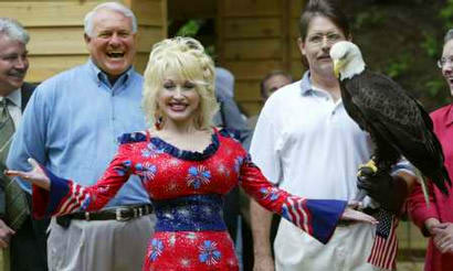 Entertainer Dolly Parton jokes alongside Challenger, a 15-year-old American Bald Eagle at the National Zoo in Washington, July 2, 2003. Parton, a contributor to the preservation of the once-endangered symbol of Amercian freedom, was present to launch the zoo's pre-July 4 Independence Day Bald Eagle Refuge Exhibit to celebrate the national bird and the 100th anniversary of the founding of the National Wildlife Refuge System. Challenger is cared for by the non-profit American Eagle Foundation, headquarted at Dollywood in Pigeon Forge, TN. Deputy Interior Secretary Steve Griles (left) and American Eagle Foundation President Al Cecere (right). — REUTERS/Jason Reed